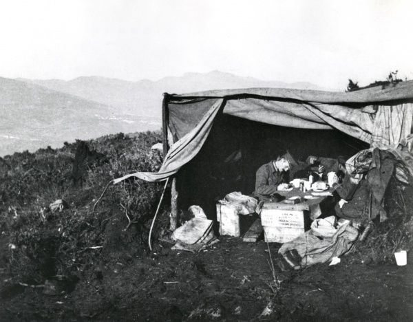 A bivouac shelter serving as Battalion Headquarters for the 5th Connaught Rangers, part of the 30th Brigade of Kosturino, on the Salonika Front during the First World War. Two men sit at a makeshift table inside. Date: 28 November 1915