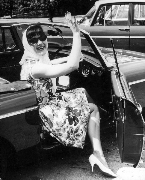 A girl in a flower print dress, white high heels, a headscarf and sunglasses steps out of a convertible car