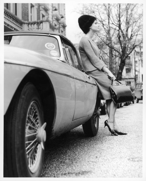 A rather stylish model in a twin suit, fur hat and matching stilettos and handbag, leaning against an MG