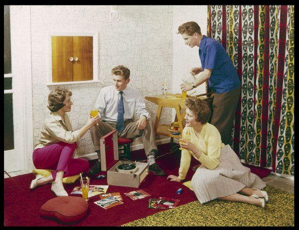 Four smartly-dressed teenagers having cocktails around a record player
