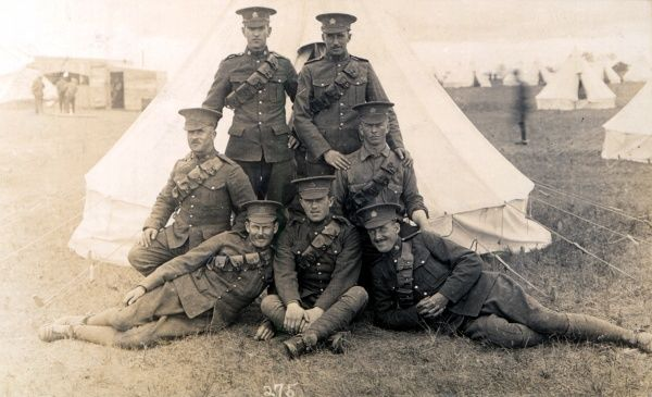 Seven smartly dressed British soldiers pose in front of a tent in the army camp