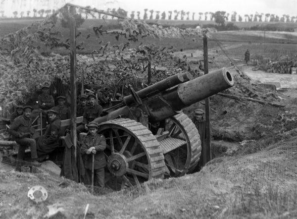 An 8 inch Mark V Howitzer in a camouflaged emplacement near Carnoy, northern France, during the Battle of Albert, First World War. The gunners are all looking at the camera. Date: July 1916