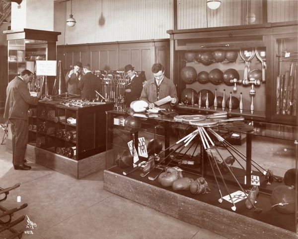 Abercrombie & Fitch Co., Sporting Goods, Interiors of Salesroom with Customers. Men looking at golfing equipment in the Abercrombie & Fitch sales room