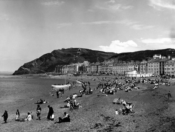 A view of the busy beach and seafront at Aberystwyth, a popular seaside resort in Ceredigion, mid Wales. Date: 1950s