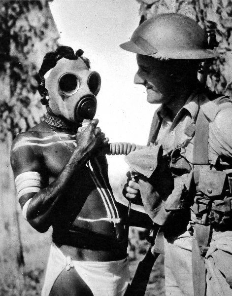 Photograph showing an aborigine in the Northern Territory of Australia trying on a gas mask during the Second World War, 1941
