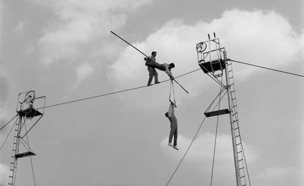 Three acrobats doing a balancing act on a high wire in the open air