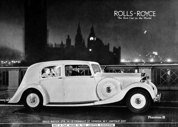 Advertisement for Rolls Royce Phantom II car, with a photograph of a chaffeur driven Rolls with two fur-wearing ladies as passengers, passing over Lambeth Bridge with the Houses of Parliament in the background at night time