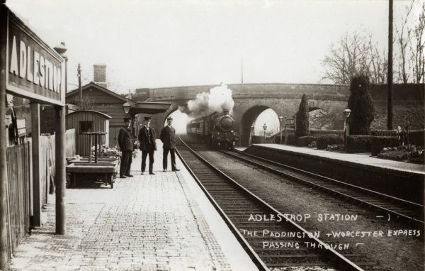 The railway station at Adlestrop, Gloucestershire. Station staff stand on the platform while the Paddington-Worcester Express steams towards the station. The location was immortalised in the Edward Thomas poem 'Adlestrop&#39