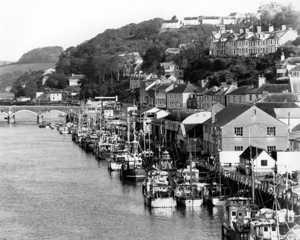 An aerial view of Looe in Cornwall, showing fishing boats, the quayside, a bridge, and various buildings stretching back up the hill