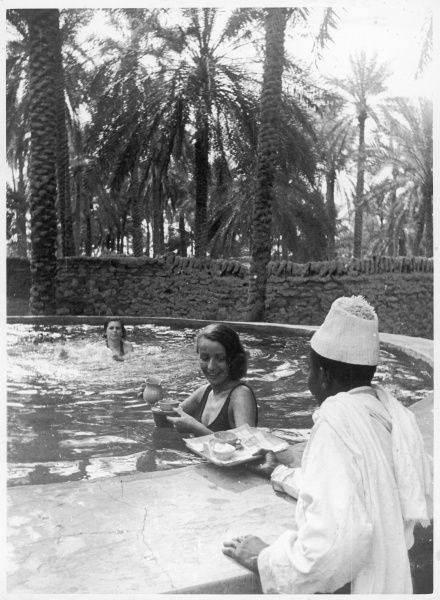 An African waiter serves two Western women relaxing in a pool shaded by palm trees