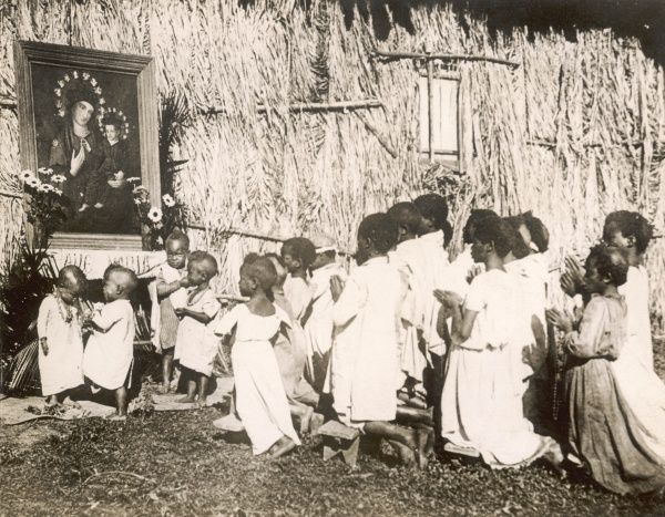 A class of black African children at a church school in the Congo, Africa, kneel before a painting of a white Madonna and Child