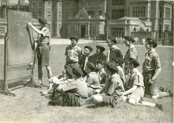 One Air Scout from St Paul's School draws a picture of a Spitfire on a blackboard for a group of other Air Scouts to learn aircraft recognition, as they sit on the lawn of their evacuated school located at Easthampstead Park