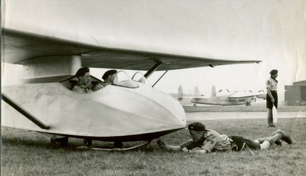 Two Scouts sit in a Slingsby T.21 while another Scout connects it to a cable prior to launch at the first Air Scout Gliding Course at Lasham. An Avro York G-ANTK can also be seen in the background