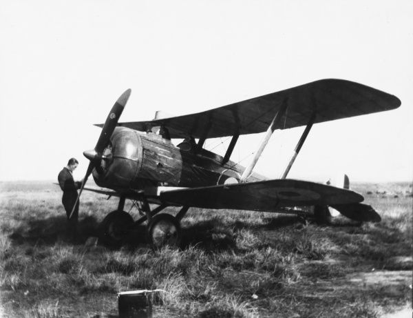 A pilot stands in front of the propellor of his Airco DH-5, a biplane fighter which had improved vision due to the the upper wing being closer to the rear of the cockpit. Date: circa 1917