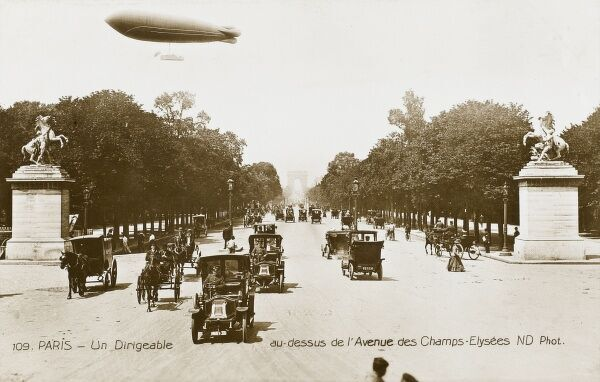 An Airship flying over the Avenue des Champs Elysees, Paris. The street is filled with early motor taxis