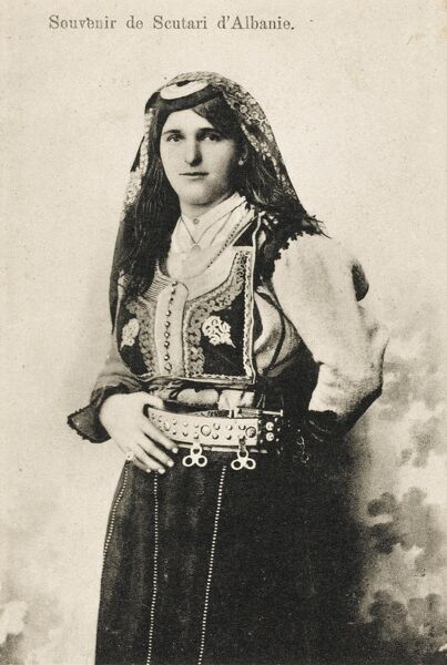 Albanian woman from Shkoder, with an embroidered waistcoat/jerkin, a substantial belt (with hoops for hanging things off it) and floral headscarf