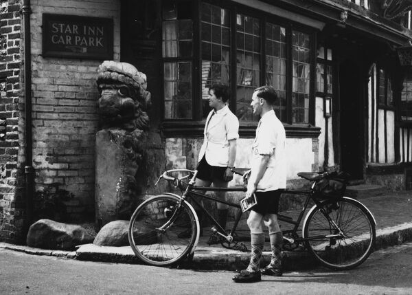 Cyclists admire a grotesque figure outside the 'Star Inn'. at Alfriston, Sussex, England. Known as the 'Alfriston Lion', it was once the figurehead of a Dutch warship