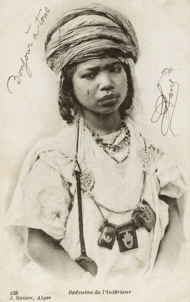 Very serious-looking Algerian Bedouin Girl, adorned with charm necklace and beads and what looks like a wooden spoon (?)