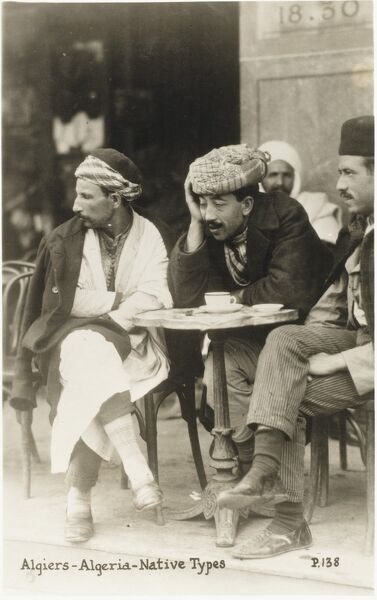 A terrific photograph of three Algerian men, seated around a small circular table outside a cafe in Algiers, Algeria