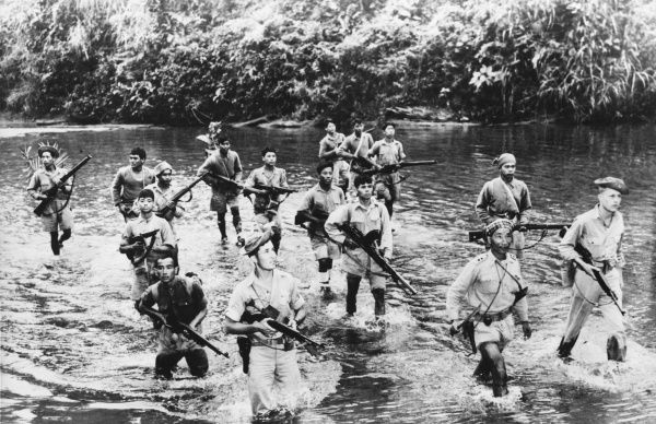 Allied scouts cross a Burmese Jungle stream. Poised for action, a scouting detachment of armed Burmese patriot fighters, accompanied by two American soldiers, cautiously wades through a Jungle stream in Northern Burma