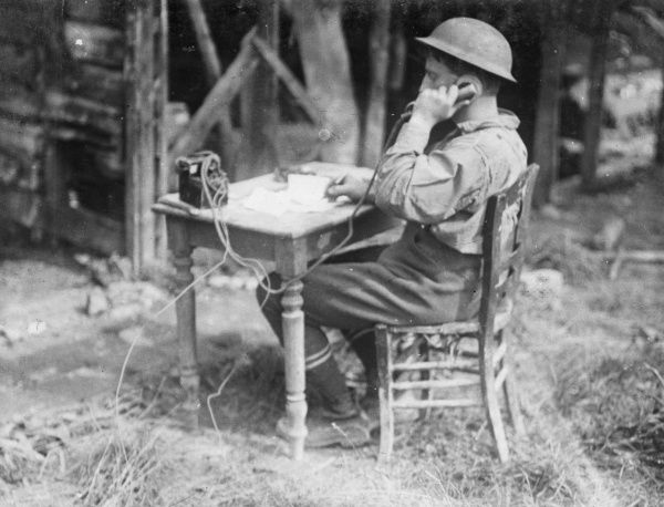An Allied soldier speaking on a field telephone while sitting at a small table in the open air during the First World War. Date: 1914-1918