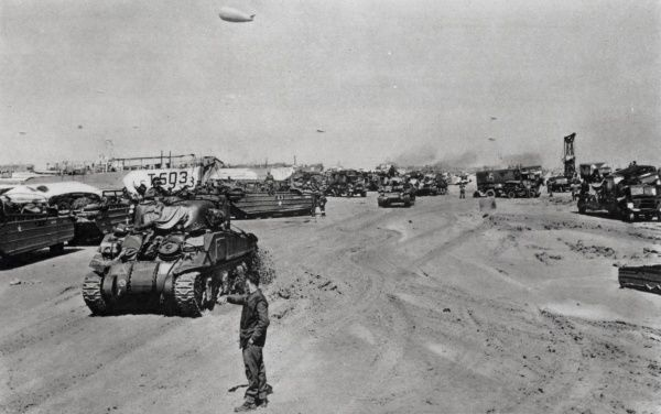 Photograph showing Allied troops and armour moving up one of the Normandy beaches, shortly after 'D-Day', 6th June 1944. At the top of the image a barrage balloon can be seen, guarding against German aerial attack