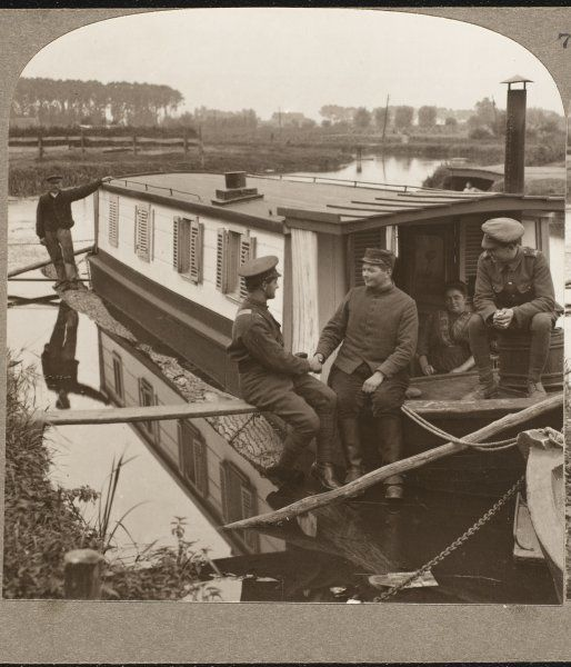 Entente Cordiale: British and either French or Belgian soldiers fraternising and relaxing on a canal boat in Flanders during the First World War