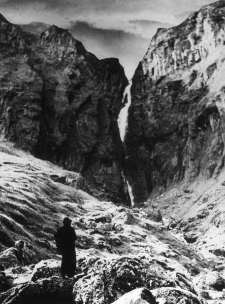 Mountainous Alpine scenery - climbing a glacier through a narrow crevasse in the rocks, through which melting water flows. Date: 1930s