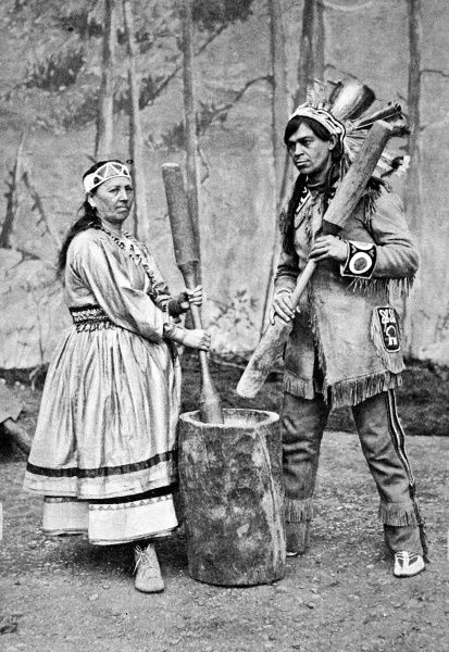 A native American and his wife pounding corn in a large pestle and mortar