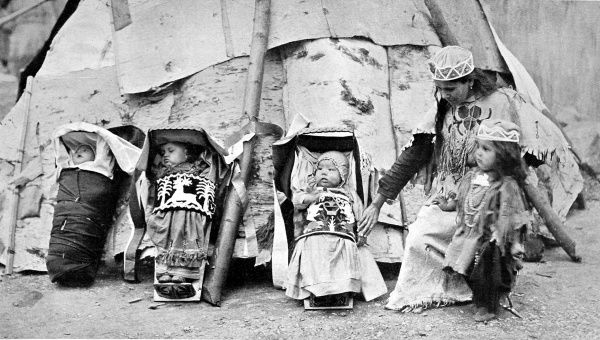 Red Indian babies, or papooses at Earl's Court. Three Red Indian babies outside a teepee, with an Indian child and woman
