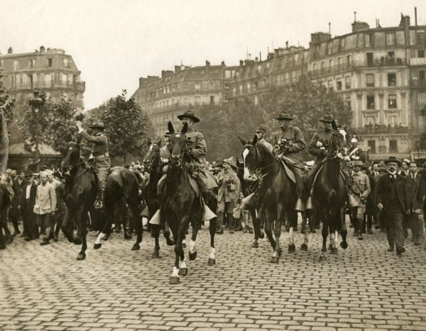 American officers riding through Paris during the First World War. Some of them are holding bouquets of flowers. Date: 1917-1918