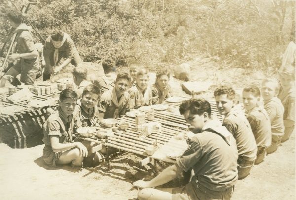 Boy scouts sit cross-legged at a low table eating food at an American Scouting Camporee