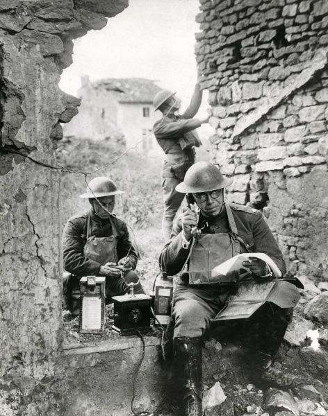 Three American soldiers using an abandoned German field telephone near St Mihiel, north eastern France, during the First World War. Date: 1918