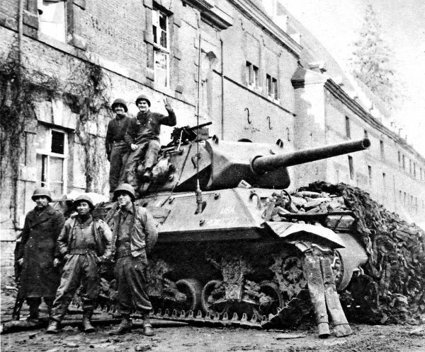Photograph showing the crew of an American tank destroyer standing beside their vehicle in Stavelot, twenty miles from Liege, during the 'Battle of the Bulge' in the winter of 1944-5