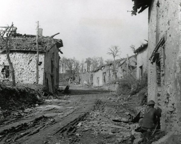 American troops in action in a street in Cunel, north eastern France, during the First World War, with damaged buildings on both sides. Date: 29 October 1918