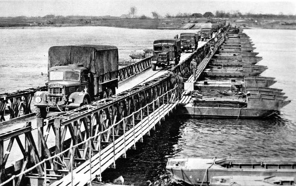 Photograph showing American trucks crossing a British-built Bailey pontoon bridge over the River Rhine into Germany, 1945