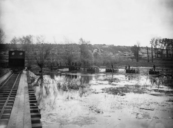 Royal Engineers bridge the Ancre Swamps at Aveluy during the latter stages of the Battle of the Somme. To the left, an engine crosses a light railway bridge