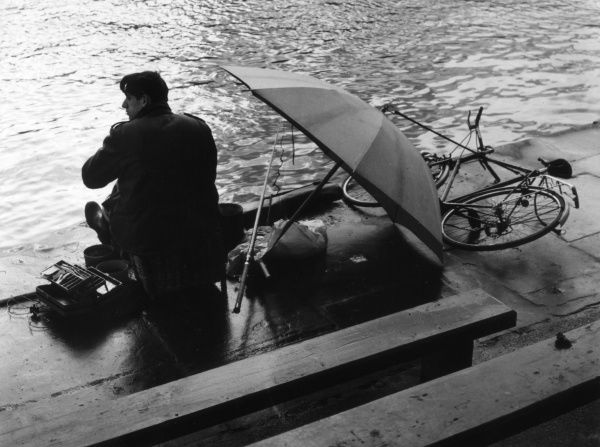 A moody study of a young man, an angler, fishing beside his umbrella and bicycle on a wet day. Date: 1960s