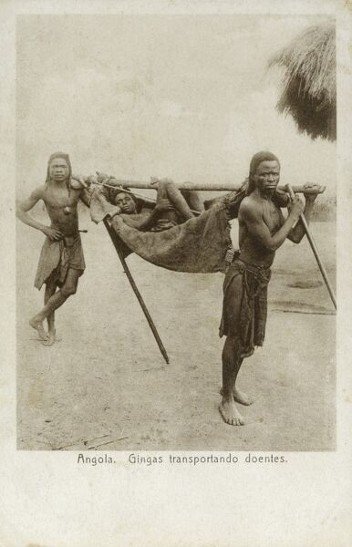 Angola - Two Njinga Tribesmen transport a sick patient in a sling held to a large pole. Date: circa 1910s