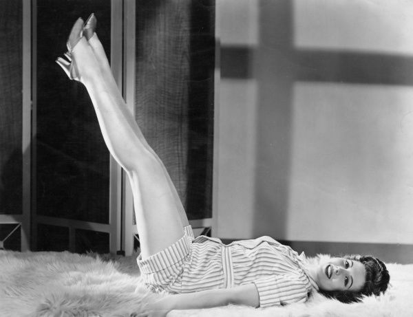 The American film actress, dancer and singer, Ann Miller (1923-2004), modelling a pair of short pyjamas while lying on a white fur rug