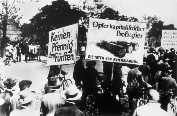 "Social democrats protest against the aristocracy. Their banners read ""Not a penny for the Princes"" and ""Victims of capitalist profit- greed&quot"