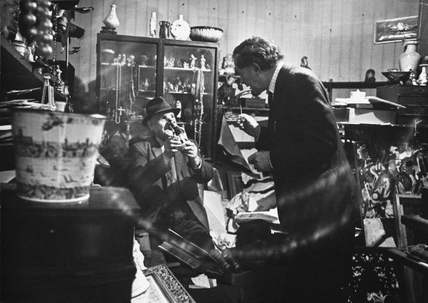 A gentleman takes off his spectacles in disbelief at the price the old man in this jumbled antique shop is asking for a figurine. Time to haggle! Date: 1960s