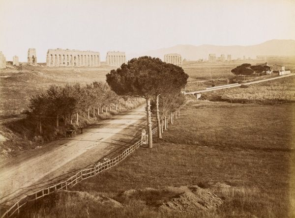 The Appian Way stretching away from Rome and the Aqueduct of Claudius in the background. Date: circa 1890