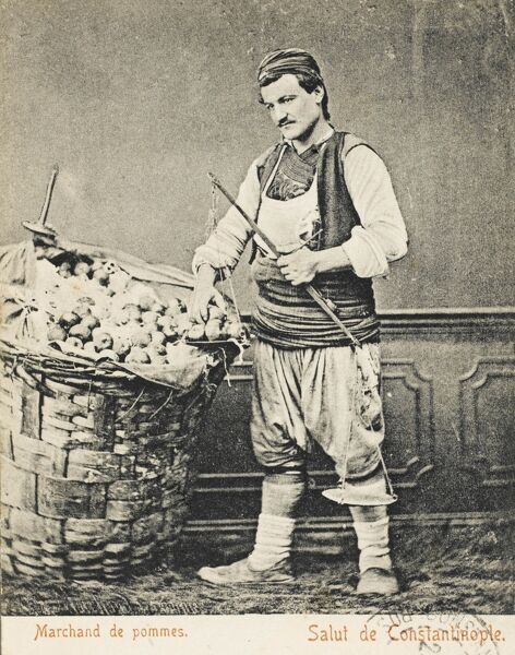 Apple seller standing alongside his large pannier, filled to the brim with fruit. The weight of this woven backpack must have been immense