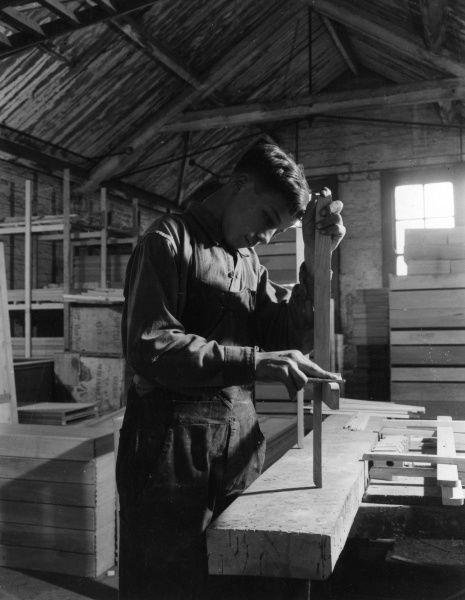 An apprentice learning his trade at a cabinet makers in Shoreditch, London