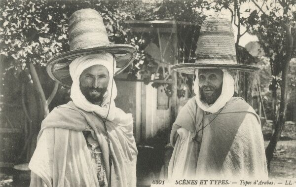 Two Arabian men in fabulous tall straw hats - southern Algeria. Taraza (or Tarazala, Tarazal) are wide-brimmed straw hats worn by both sexes in Morocco and Algeria