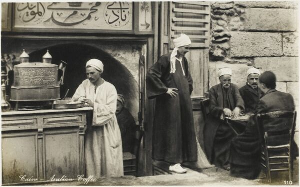 Arabian street Cafe scene - Cairo, Egypt. Men sit and drink and chat on the street and in the alcove recess behind the coffee / tea stall