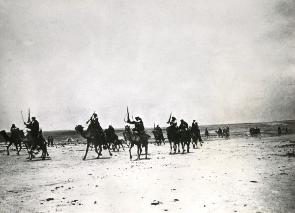 Arabs riding camels across the desert in Palestine during the First World War. Some are holding their rifles up in the air. Date: 1914-1918