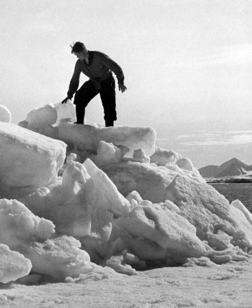 An arctic bear hunter, on top of a mound of snow, searching for the body of the bear he has just shot through the skull