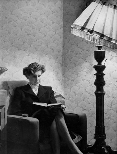 A smart woman, sitting in an armchair, reading a book under the light of a standard lamp with a tilted lampshade. Date: 1940s